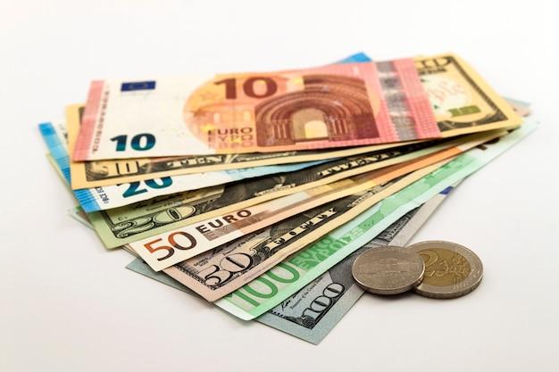 Le banconote in dollari usa e le euro fatture si sono diffuse miste su fondo bianco.