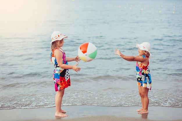 Le belle bambine adorabili insieme le ragazze allegre di bellezza femminile casuale di stile di vita del ritratto che si tengono per mano sul mare giocano della spiaggia. concetto di infanzia