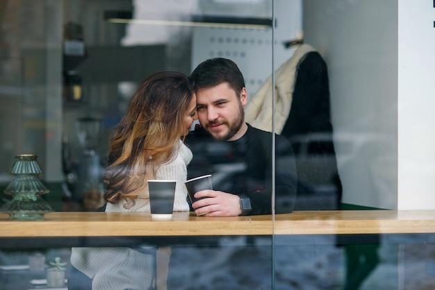 Le belle coppie caucasiche bevono il caffè ad una data e si divertono insieme.