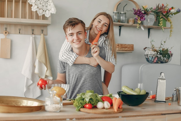 Le belle coppie preparano l'alimento in una cucina