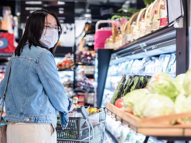 Le belle donne asiatiche indossano la maschera con il carrello nel supermercato si distinguono dalle altre persone per mantenere l'allontanamento sociale di sicurezza come nuovo concetto di stile di vita normale