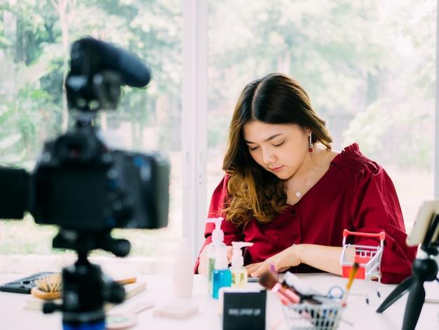 Le belle donne di vloger usano internet online per rivedere la sua marca di cosmetici