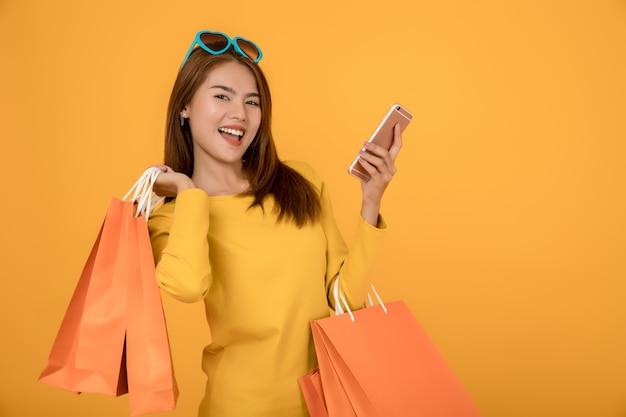 Le belle donne fanno shopping in estate con sacchetti di carta blu