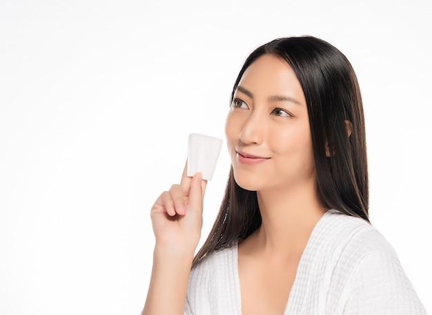 Le belle donne puliscono il fronte con cotone su fondo bianco