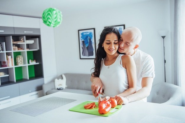 Le belle giovani coppie macinano insieme le verdure nella cucina.