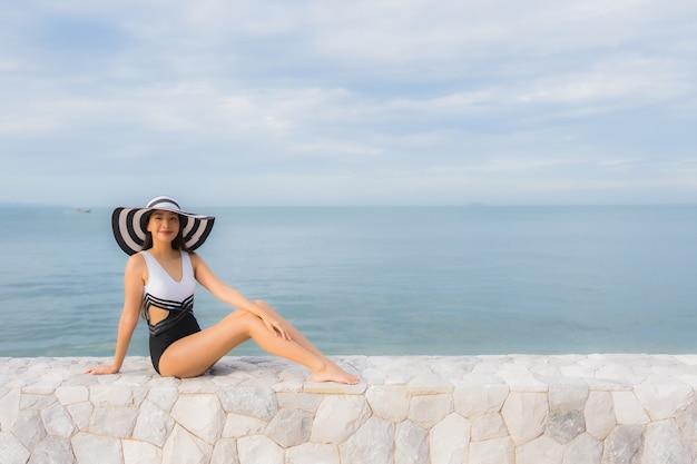 Le belle giovani donne asiatiche del ritratto si rilassano il sorriso felice intorno all'oceano della spiaggia del mare