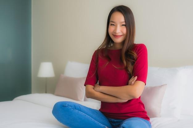 Le belle giovani donne asiatiche del ritratto sorridono felici sul letto