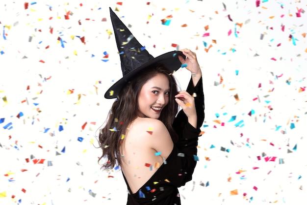 Le belle giovani donne in strega nera halloween costumes sul partito sopra priorità bassa bianca