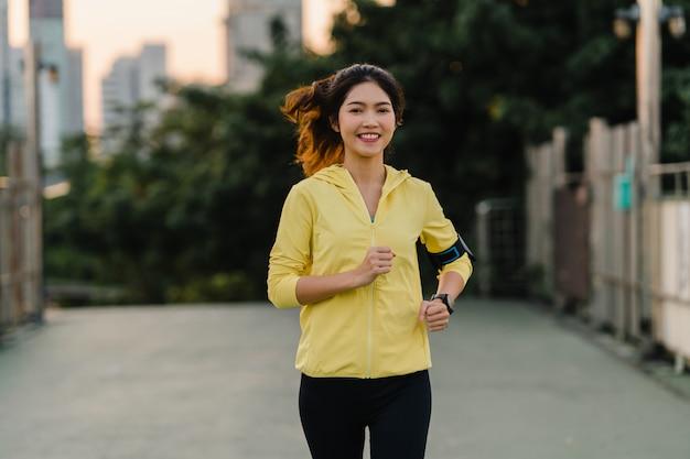 Le belle giovani esercitazioni di funzionamento di signora dell'atleta dell'asia risolvono nell'ambiente urbano. la ragazza teenager giapponese che indossa gli sport copre sul ponte del passaggio pedonale nel primo mattino. stile di vita sportivo attivo in città.