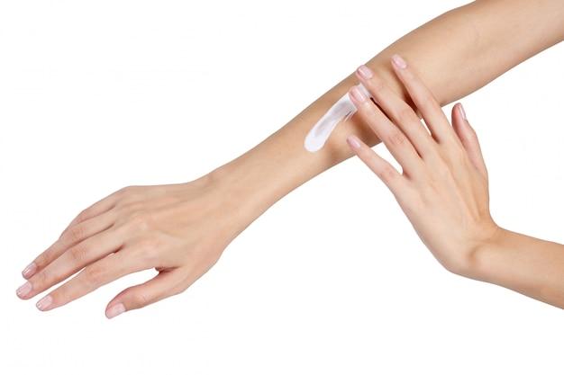 Le belle mani della donna che si rilassano con applicano la lozione a disposizione isolata su fondo bianco