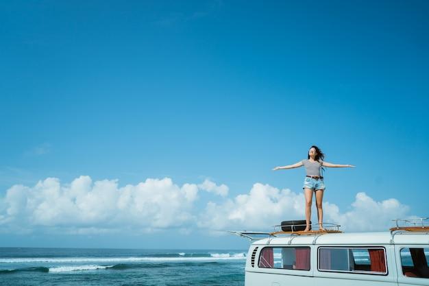 Le belle mani di aumento della donna godono della natura di viaggio stradale che sta su van roof
