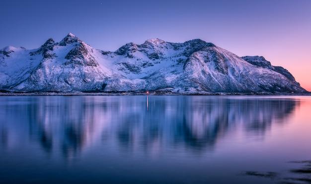Le belle montagne innevate e il cielo variopinto hanno riflesso in acqua al crepuscolo. paesaggio invernale con mare, rocce innevate, cielo viola, riflesso, al tramonto.