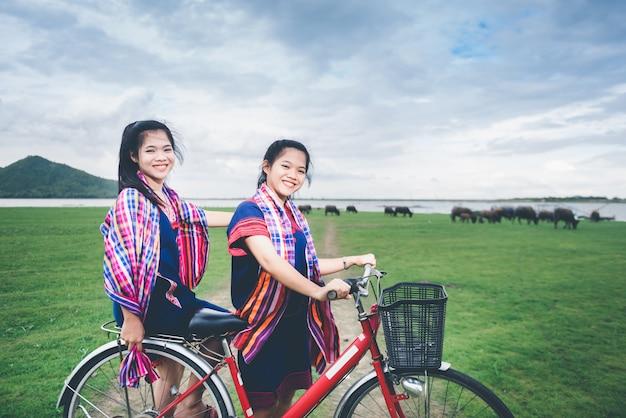 Le belle ragazze asiatiche godono del viaggio alla campagna della tailandia guidando sulla bicicletta