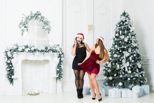 Le belle ragazze con i cappelli di santa nel natale hanno decorato la stanza. festa di capodanno.