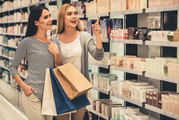Le belle ragazze con i sacchetti della spesa stanno sorridendo.