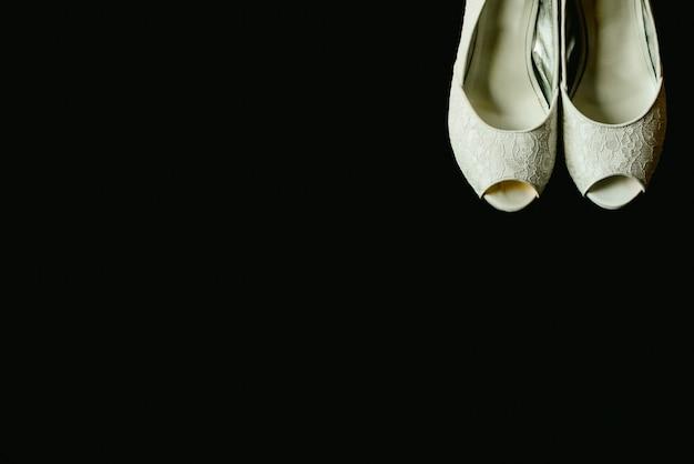 Le belle scarpe bianche di nozze in un angolo su fondo nero isolato, copiano lo spazio.