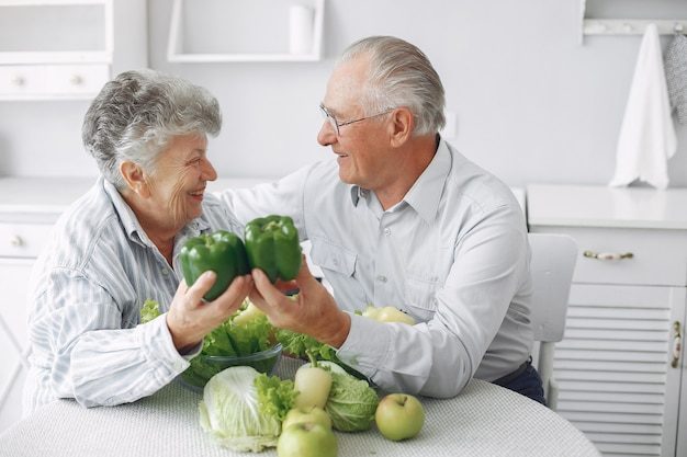 Le belle vecchie coppie preparano l'alimento in una cucina