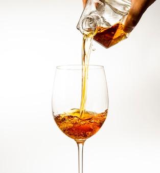 Le bevande alcoliche vengono versate in un bicchiere di decanter su uno sfondo chiaro