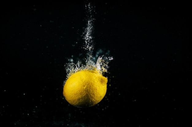 Le bolle si alzano intorno al limone giallo che cade nell'acqua