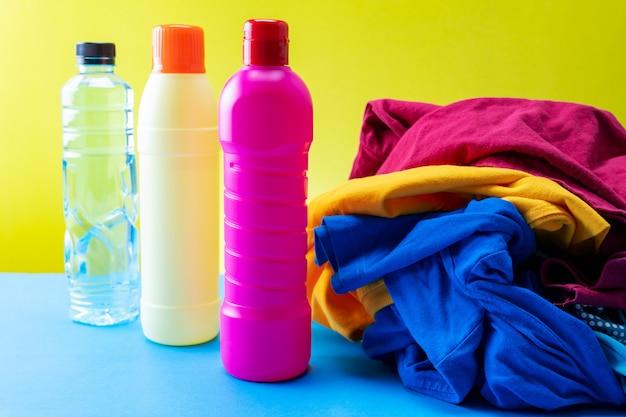 Le bottiglie di plastica dei prodotti per la pulizia hanno messo con i vestiti del mucchio sulla tavola blu fondo giallo.