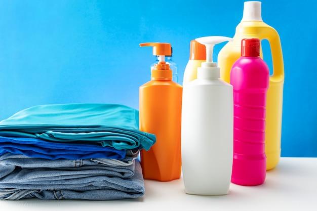 Le bottiglie di plastica dei prodotti per la pulizia hanno messo sulla tavola bianca.