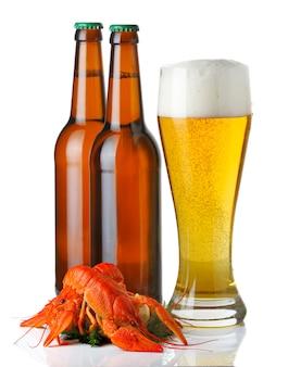Le bottiglie e la tazza di birra leggera e le aragoste ammucchiano isolato