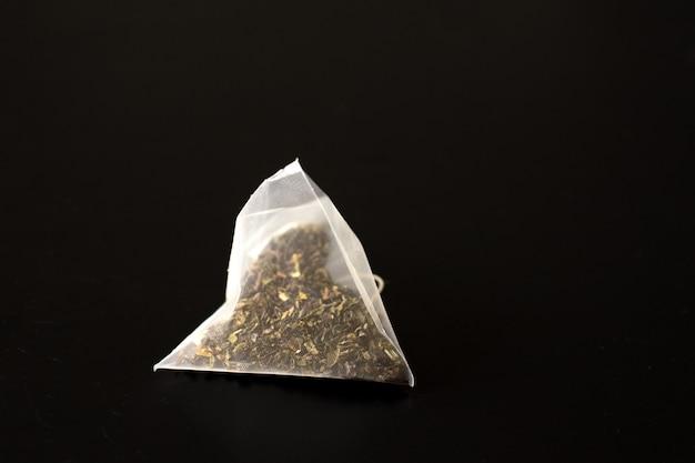 Le bustine di tè isolate sul nero.
