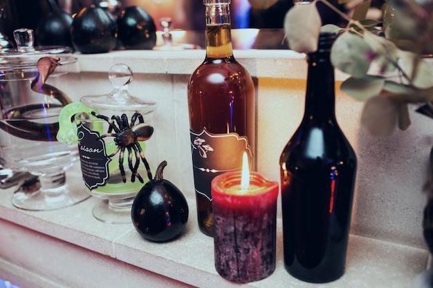 Le candele nere si stendono tra le bottiglie con vino