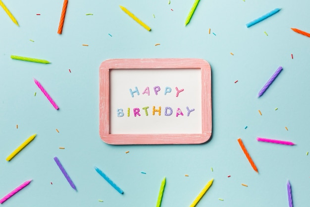 Le candele variopinte e spruzza sparse intorno alla struttura bianca di buon compleanno su fondo blu