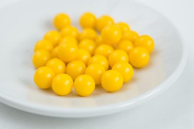 Le capsule di vitamina c sono su un piatto su uno sfondo bianco
