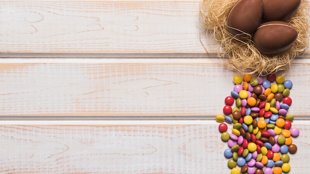 Le caramelle multicolori delle gemme si avvicinano alle uova di cioccolato sul nido sopra lo scrittorio di legno