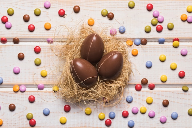 Le caramelle variopinte della gemma circondate intorno alle uova di pasqua del cioccolato annidano sulla tavola di legno