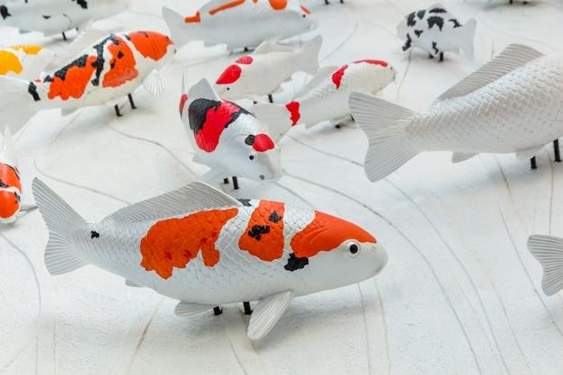 Le carpe pescano o la statua del pesce di koi sulla parete del cemento per decorano, lo stucco handcraft del pesce della carpa di koi sulla parete