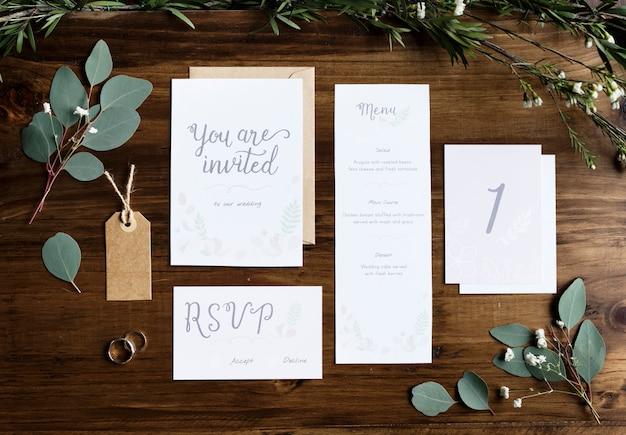 Le carte delle carte dell'invito di nozze che mettono su tavola decorano con le foglie