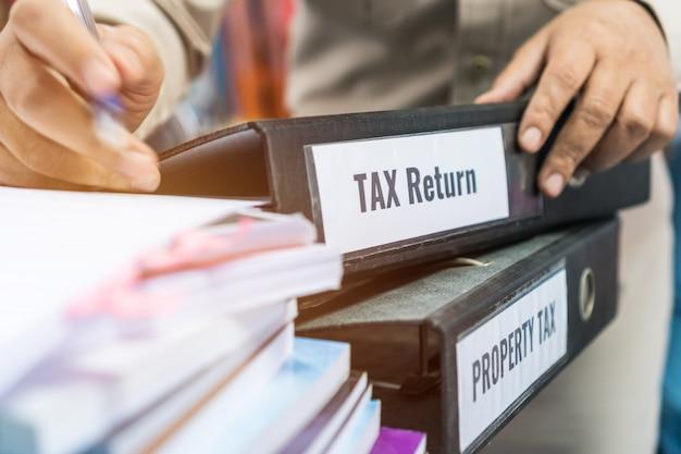 Le cartelle delle dichiarazioni dei redditi e delle imposte patrimoniali si impilano con il raccoglitore di etichette nero sul rapporto di riepilogo del documento cartaceo