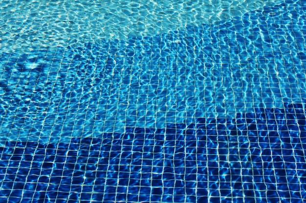 Le caustiche del fondo del mosaico della piscina si increspano come l'acqua di mare. flusso con onde, sport e relax concetto. sfondo estivo texture della superficie dell'acqua. vista dall'alto.
