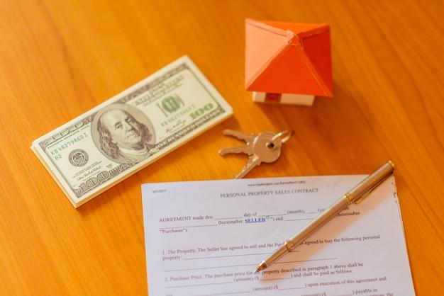 Le chiavi della casa sull'accordo di noleggio o il contratto di acquisto di casa con lo sfondo della proprietà immobiliare.