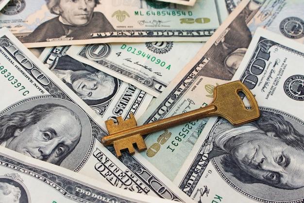Le chiavi su uno sfondo di denaro.