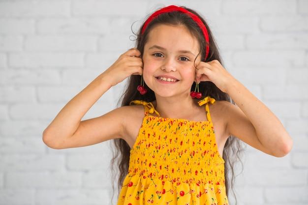 Le ciliege sveglie sorridenti della tenuta della ragazza vicino all'orecchio gradiscono gli orecchini