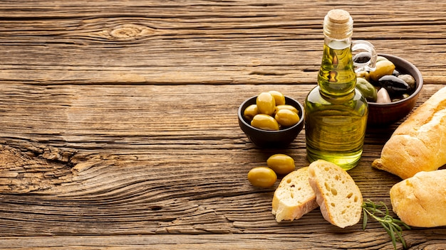 Le ciotole di oliva dell'angolo alto impanano le fette e botte dell'olio con lo spazio della copia