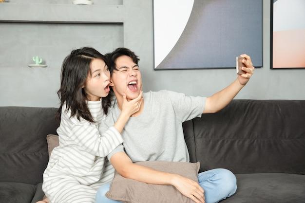 Le coppie adorabili scattano foto con i loro telefoni cellulari a casa.