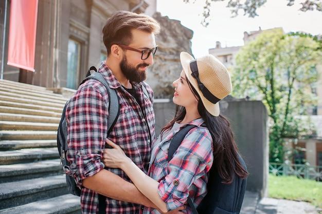 Le coppie adorabili stanno alle scale e si abbracciano. sembrano e sorridono. i turisti hanno degli zaini. è una bella giornata di sole fuori.