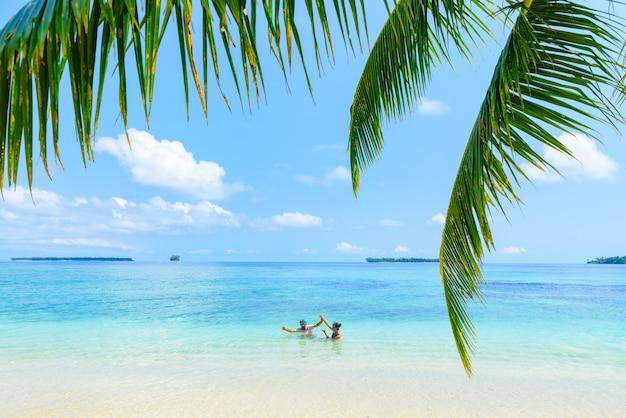 Le coppie adulte felici che si divertono in turchese innaffiano il mar dei caraibi sulla spiaggia tropicale
