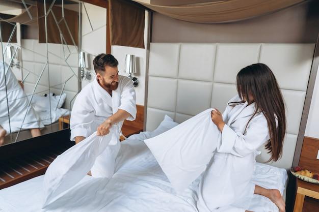 Le coppie allegre si divertono nella lotta della camera da letto con i grandi cuscini a casa