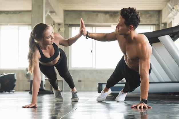 Le coppie amano il giovane allenamento dell'uomo e delle donne di forma fisica che si esercitano insieme. allenamento con i pesi e concetto di programma cardio.