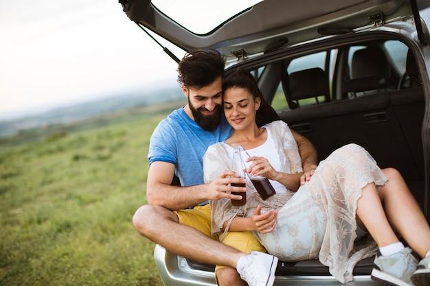 Le coppie amorose che si siedono nell'automobile trank durante il viaggio nella natura