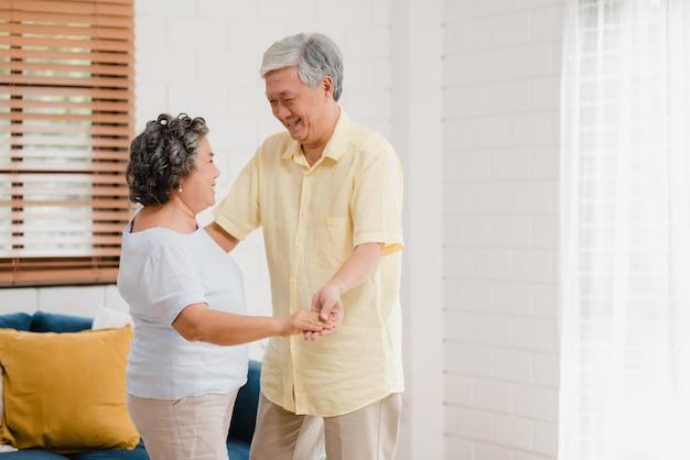 Le coppie anziane asiatiche che ballano insieme mentre ascoltano la musica in salone a casa, coppie dolci godono del momento di amore mentre si divertono una volta rilassato a casa.