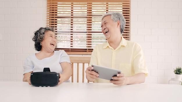 Le coppie anziane asiatiche facendo uso della compressa e del simulatore di realtà virtuale che giocano in salone, coppia ritenente felice facendo uso di tempo insieme che si trova sulla tavola a casa.