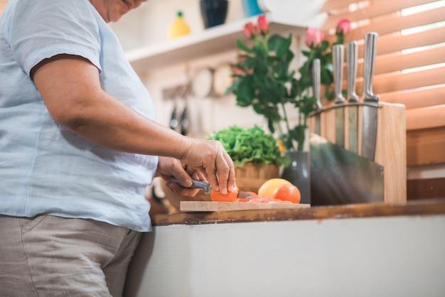 Le coppie anziane asiatiche tagliano i pomodori preparano l'ingrediente per la fabbricazione dell'alimento nella cucina