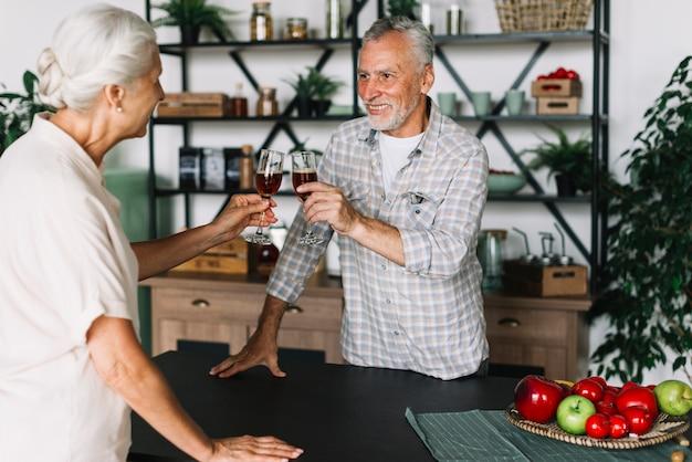 Le coppie anziane sorridenti che tostano l'alcool fuma nella cucina